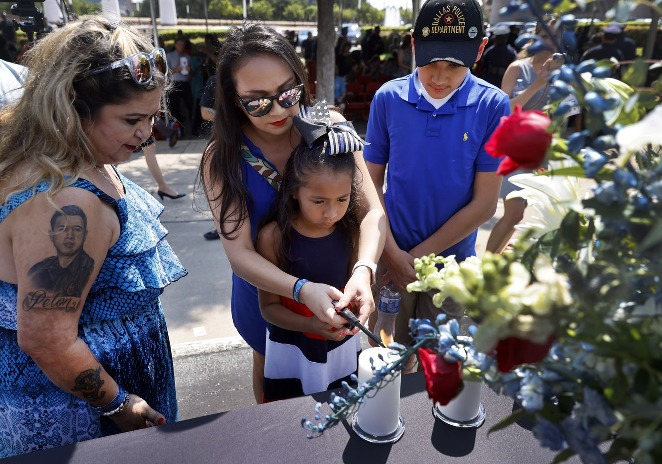 """Kristy Zamarripa, widow of fallen Dallas officer Patricio """"Patrick"""" Zamarripa, helps their daughter Lyncoln, 7, light a candle in his honor following the annual Police Memorial Day in which the Department honored officers who died in the line of duty at the Dallas Police Memorial in downtown Dallas, Wednesday, July 7, 2021.  His stepson Dylan Hoover is pictured on the right and his mother Valerie Zamarripa, left, joined in the remembrance on the 5th anniversary of the July 7th ambush. (Tom Fox/The Dallas Morning News)"""