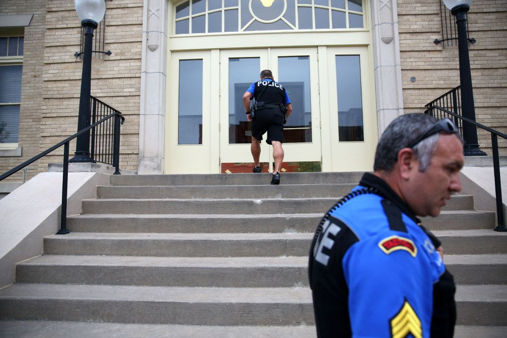 McKinney neighborhood police officer Randy Patton walks up the steps of the historic McKinney courthouse while on patrol with Sgt. Damian Guerrero in downtown McKinney. (Rose Baca/The Dallas Morning News)