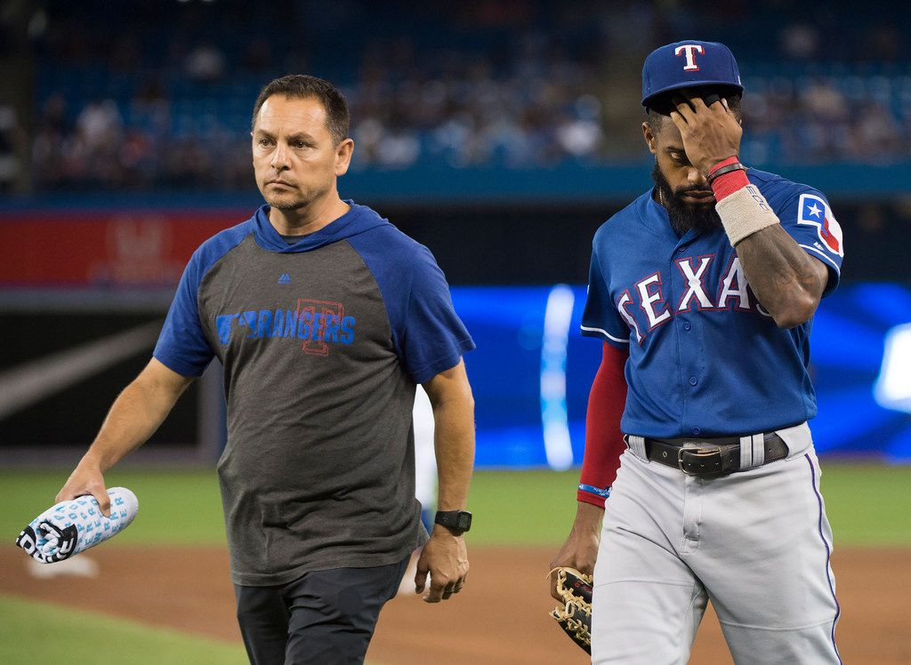 Texas Rangers center fielder Delino DeShields, right, walks back to the dugout with the trainer after making a diving catch on a hit by Toronto Blue Jays catcher Reese McGuire during the fourth inning of a baseball game, Tuesday Aug. 13, 2019 in Toronto. (Nathan Denette/The Canadian Press via AP)