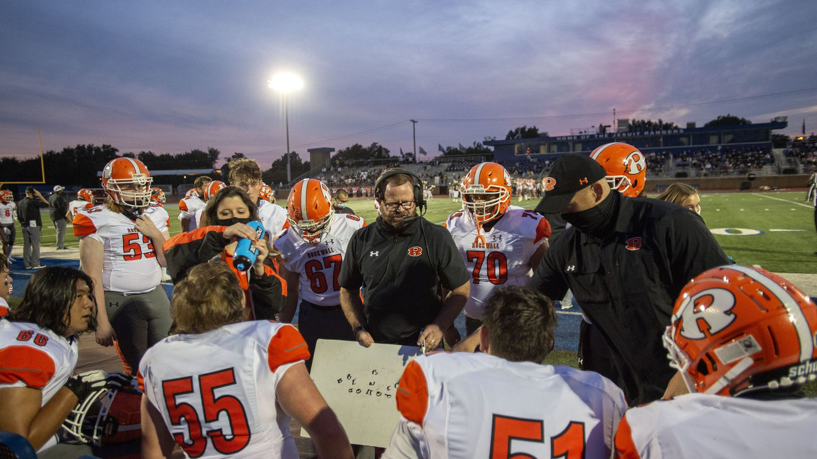 Rockwall offensive line coach Rusty Brackett, center, instructs his players on the sidelines in the first half of a high school football game against Jesuit on Friday, October 2, 2020 at Postell Stadium in Dallas.
