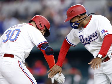 Texas Rangers batter Nate Lowe (30) is congratulated on his two-run homer by third base coach Tony Beasley in the third inning against the Toronto Blue Jays at Globe Life Field in Arlington, Tuesday, April 7, 2021. (Tom Fox/The Dallas Morning News)