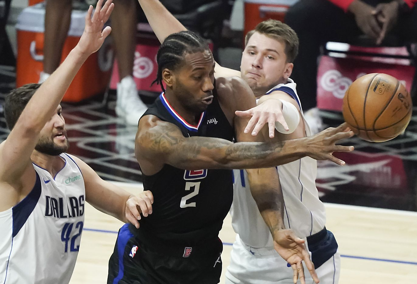 Dallas Mavericks guard Luka Doncic (77) and forward Maxi Kleber (42) defend against LA Clippers forward Kawhi Leonard (2) during the first half of an NBA playoff basketball game at Staples Center on Tuesday, May 25, 2021, in Los Angeles.