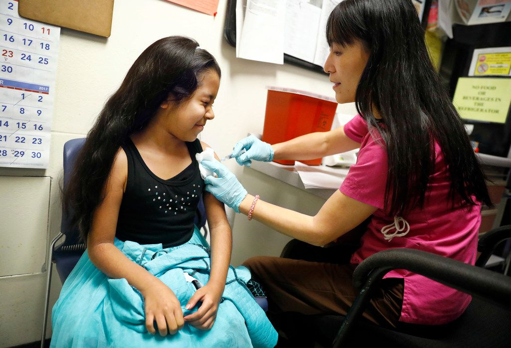 Hailey Esquivel, 8, winces as she receives an influenza shot from nurse Jenny Wang at the Dallas County Health and Human Services Immunization Clinic in Dallas, Tuesday, December 20, 2017. The Esquivel children are receiving their flu shots before traveling to Mexico for Christmas. (Tom Fox/The Dallas Morning News)