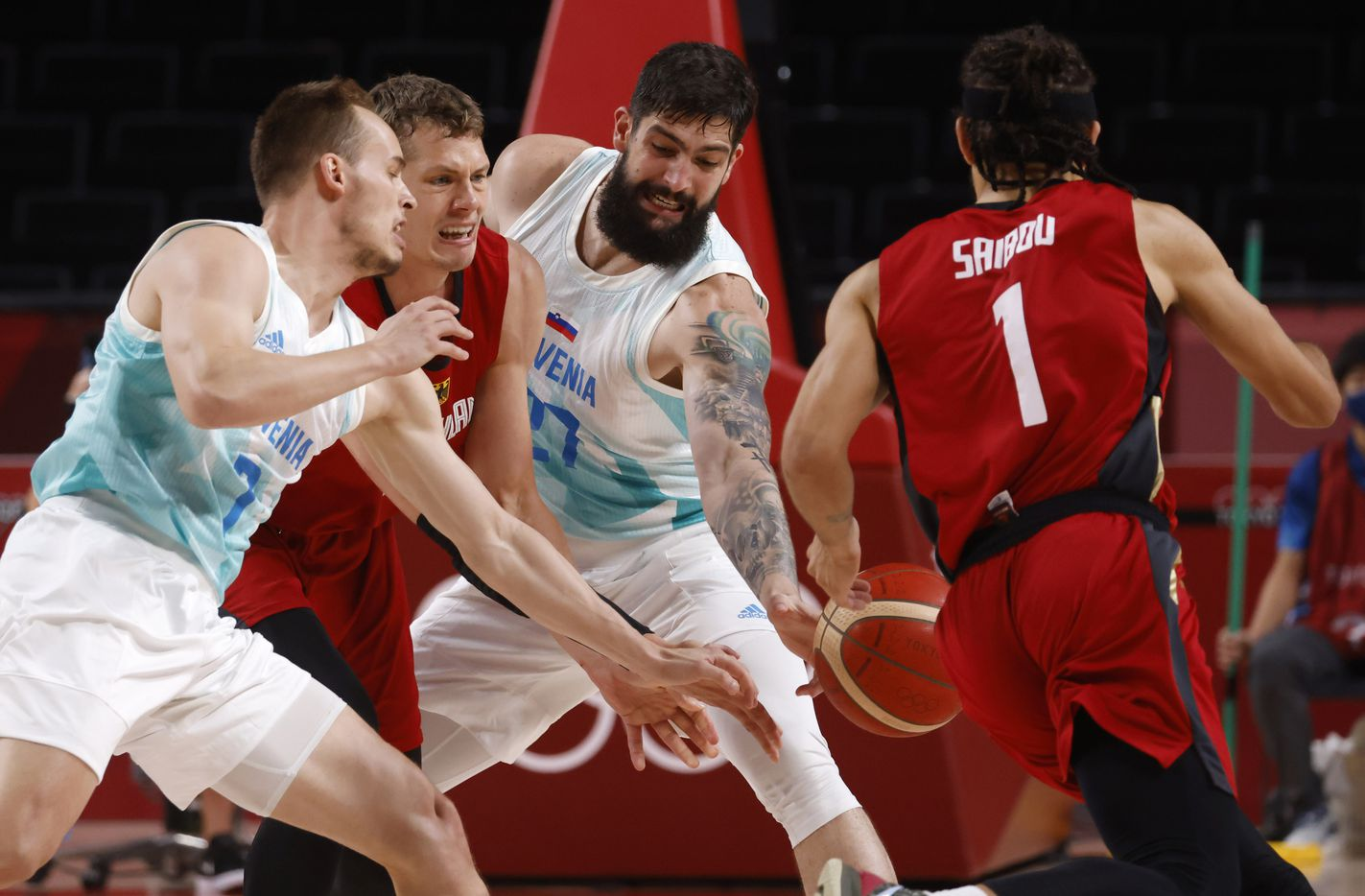 Slovenia's Ziga Dimec (27) knocks the ball away from Germany's Moritz Wagner (13) as he attempts to pass to Joshiko Saibou (1) as Slovenia's Klemen Prepelic (7) defends during the first half of play of a quarter final basketball game at the postponed 2020 Tokyo Olympics at Saitama Super Arena, on Tuesday, August 3, 2021, in Saitama, Japan. (Vernon Bryant/The Dallas Morning News)