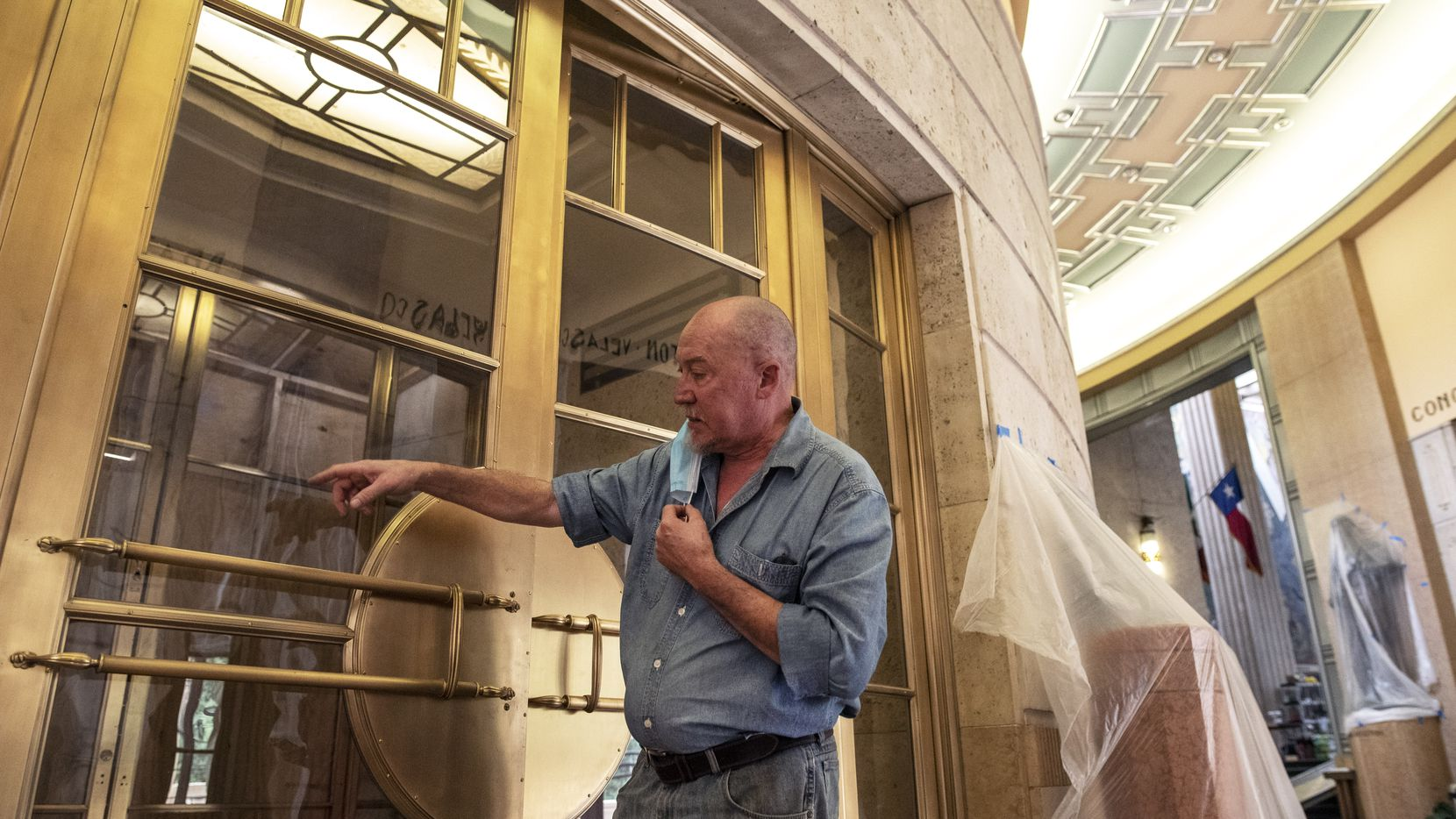 Art conservator Michael Van Enter explains the process of hand polishing a brush finish on one of the sets of massive doors at the Hall of State. His team also was responsible for restoring the intricate silver leaf in the ceiling.
