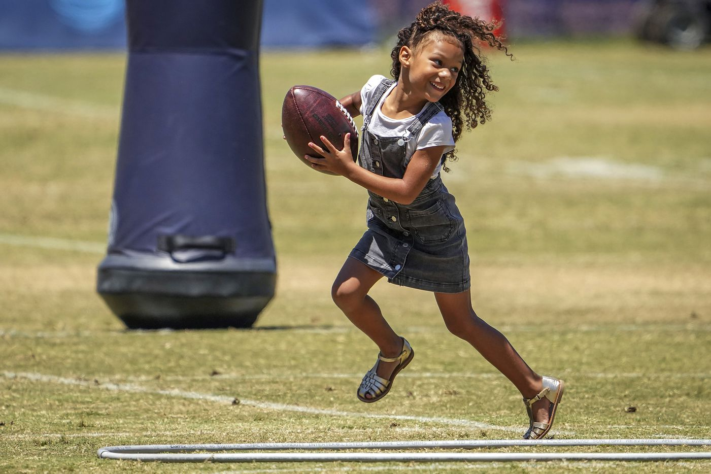 Sophia Gregory, daughter of Dallas Cowboys defensive end Randy Gregory, plays on the field after a practice at training camp on Sunday, Aug. 1, 2021, in Oxnard, Calif.