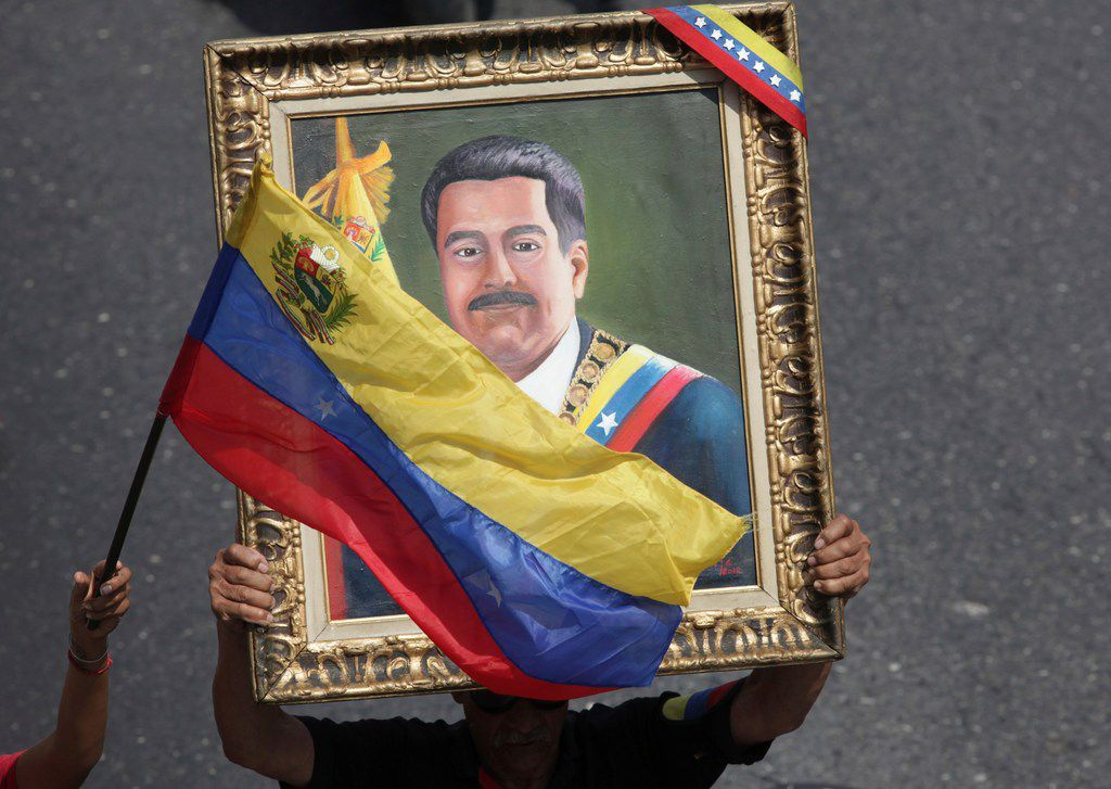 This May 1, 2019 file photo shows a government supporter holding a framed image of Venezuelan President Nicolas Maduro during an anti-imperialist rally, in Caracas, Venezuela. The Trump administration is facing a July 27, 2019 deadline to renew a license granting Chevron permission to continue operating in Venezuela despite U.S. sanctions aimed at ousting Maduro by choking off revenue from the world's largest crude reserves. (AP Photo/Boris Vergara, File)