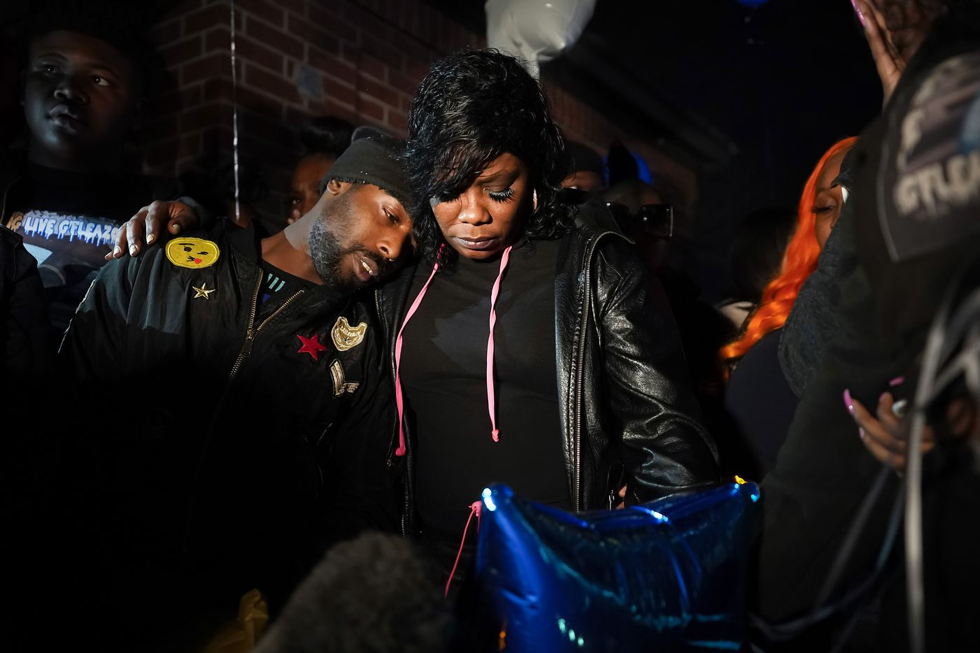 """Monique Mitchell (center) is consoled during a vigil for her son Marc """"Flea"""" Strickland, an 18-year-old victim of a shooting at Dallas ISD basketball game, at Bushman Park on Sunday, Jan. 19, 2020."""