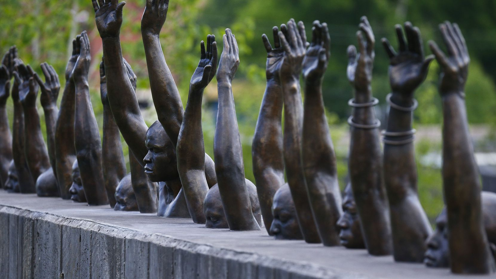 """The bronze statue """"Raise Up"""" is part of the display at the National Memorial for Peace and Justice, a memorial in Montgomery, Ala., honoring thousands of people killed in lynchings."""