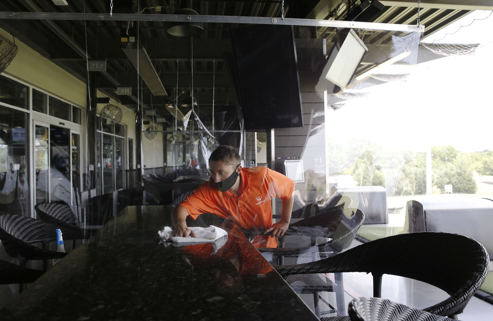 On the other side of a recently installed plastic liner, Kyle Harris cleans tables and seats at Topgolf in The Colony, on Friday, May 22, 2020.