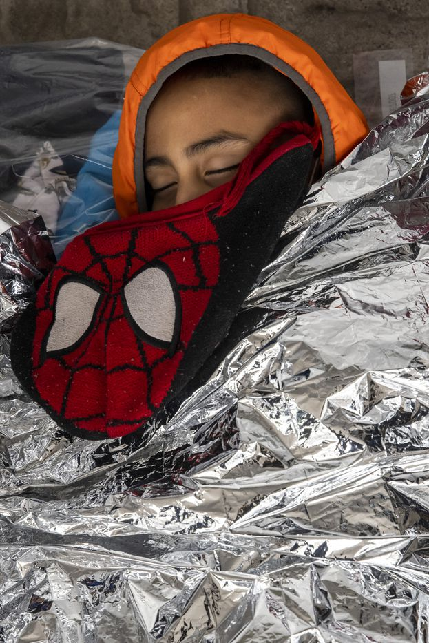 Leonel Flores, age seven, sleeps on the ground while tucked into a space blanket in the plaza near the international bridge leading into Reynosa, in Mexico. Flores and his mother, from Honduras, were expelled from the United States overnight under Title 42 — a pandemic-related public order still in place and left over from the Trump administration. However, the Mexican government in Tamaulipas isn't allowing the return of migrant families with children age six or under.