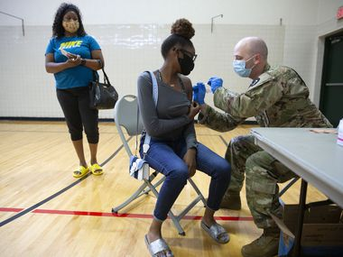 Nijah Cook (CQ), 16, receives the Covid vaccine from Spc. Derek Hurtado (right) as mother Vinnetta Cook waits for her shot at Kiest Recreation Center in Dallas, Texas on Saturday, June 5, 2021.