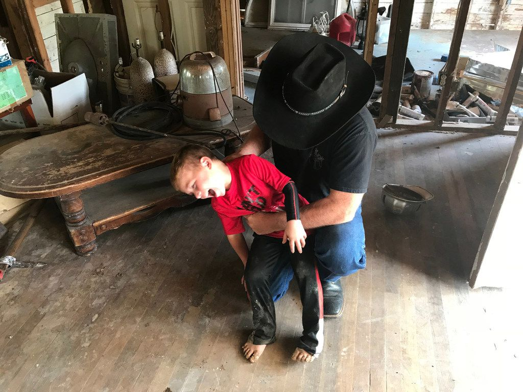 Chris Ward tickles his son, 6-year-old Ryland Ward, at the family home he and his brother are remodeling in La Vernia, Texas, on April 2, 2018. Ward lost his wife and two daughters in the shooting at the First Baptist Church of Sutherland Springs. Ryland, who was shot four times in the massacre, has undergone several surgeries and hours of physical therapy. (Lauren McGaughy/Staff)