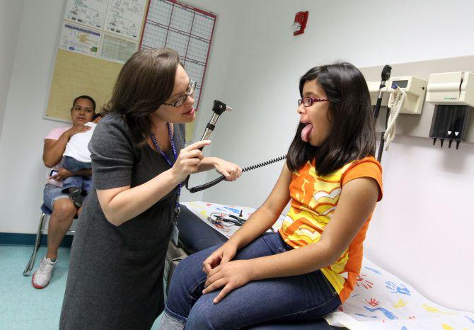 La doctora Emily Sloan le realiza un examen médico a Verónica Aguilar, de 10 años, en la Clínica Los Barrios Unidos. Debido a la pandemia, se anunció que atenderán solo mediante telemedicina.