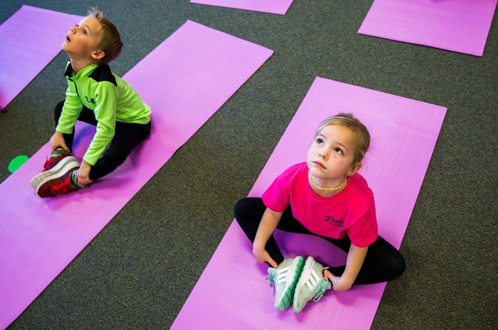 Kindergarten students Bentley Baird (left) and Charlotte Mayer are put through their paces in yoga class.