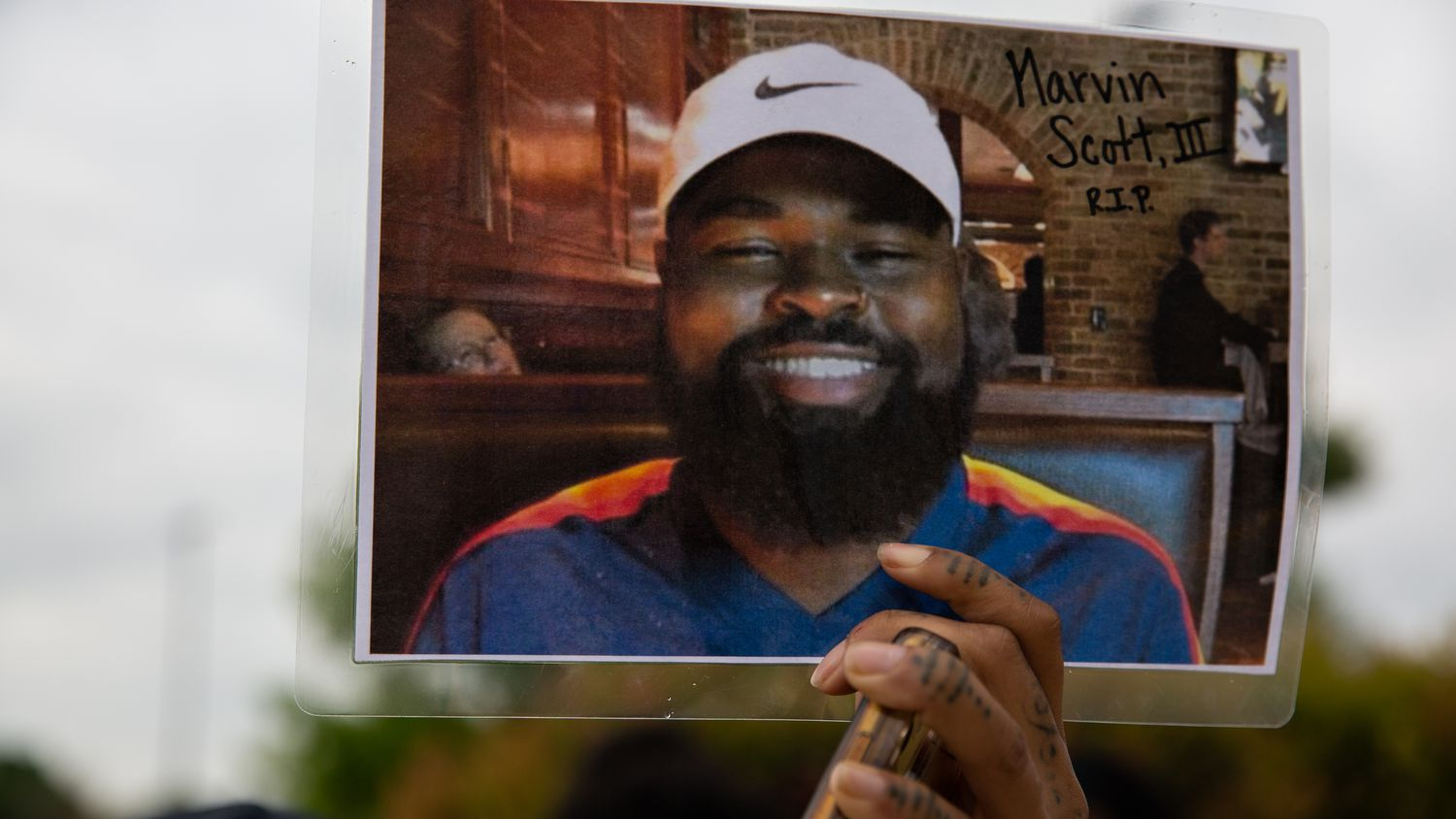 Renee White held up a photo of Marvin Scott III after a news conference on April 28, 2021, while demanding that police officers at the Collin County Courthouse arrest the officers involved in Scott's in-custody death.