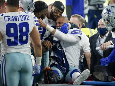 Dallas Cowboys quarterback Dak Prescott lis consoled by teammates as he leaves the field on a cart after beig injured on a tackle by New York Giants cornerback Logan Ryan during the third quarter of an NFL football game at AT&T Stadium on Sunday, Oct. 11, 2020, in Arlington. Prescott was injured o the play when Ryan came down on his right leg and left the game.