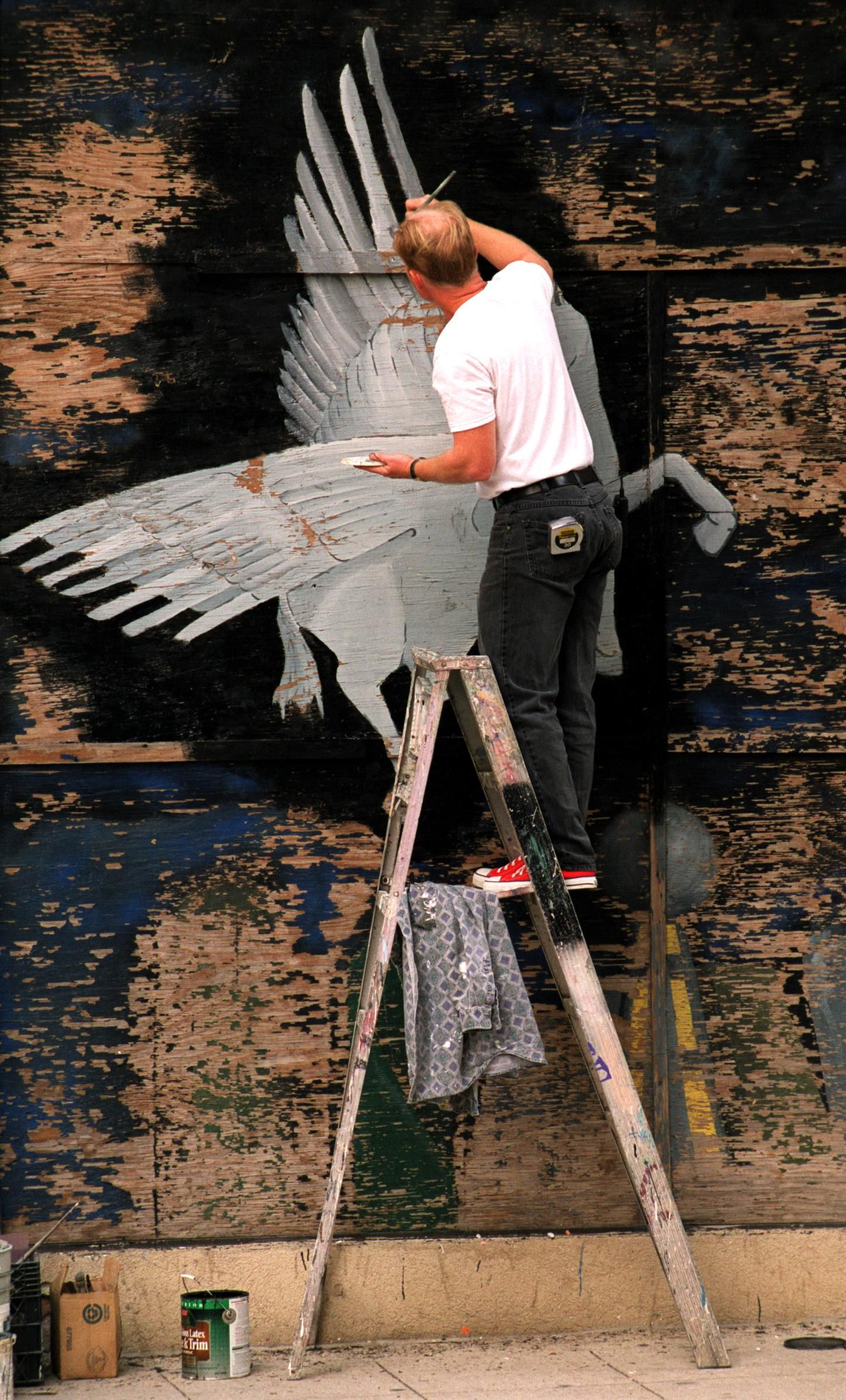 Thursday, Dec. 30, 1999: Frank Campagna, who works for Entertainment Collaborative, cleans up a Pegasus mural at the corner of Main and Akard in downtown Dallas.  Preparations were in the final stages for the millennium celebration.