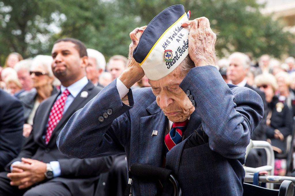 Pearl Harbor veteran Aaron Cook, 94, of Houston, who was at Ford Island during the attack, puts on his cap during a 75th Anniversary of Pearl Harbor commemoration at the George Bush Presidential Library on Wednesday, Dec. 7, 2016, in College Station, Texas. (Smiley N. Pool/The Dallas Morning News)