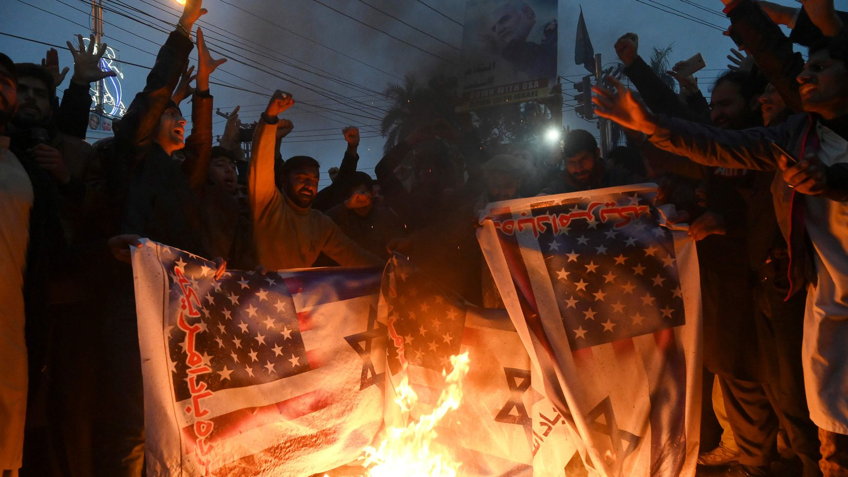 Pakistanis burn U.S. and Israeli flags in a protest against the killing of top Iranian commander Qassem Soleimani.