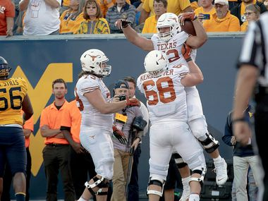 Texas offensive lineman Samuel Cosmi (52) celebrates a touchdown against West Virginia during an NCAA college football game on Saturday, Oct. 5, 2019, in Morgantown, W. Va. (Nick Wagner/Austin American-Statesman via AP)