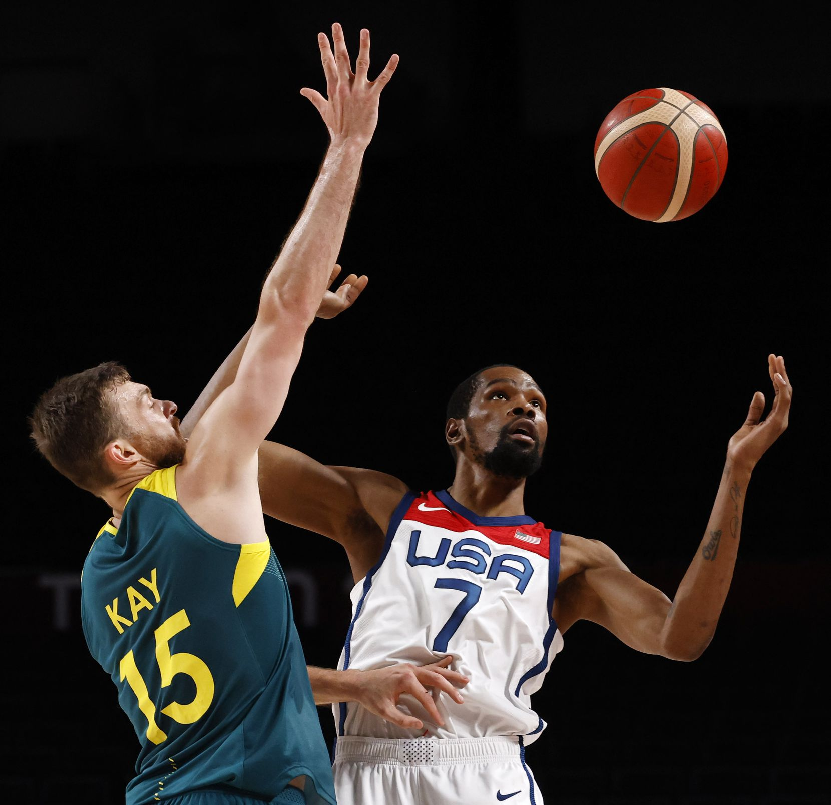 USA's Kevin Durant (7) attempts to gain control of the ball as he is defended by Australia's Nic Kay (15) during the first half of a men's basketball semifinal at the postponed 2020 Tokyo Olympics at Saitama Super Arena, on Thursday, August 5, 2021, in Saitama, Japan. USA defeated Australia 97-78 to advance to the gold medal game. (Vernon Bryant/The Dallas Morning News)