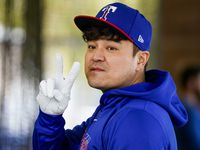 Texas Rangers outfielder Shin-Soo Choo motions to a teammate as he waits his turn in the batting cage on the day pitchers and catchers reported for spring training at the team's training facility on Tuesday, Feb. 11, 2020, in Surprise, Ariz.