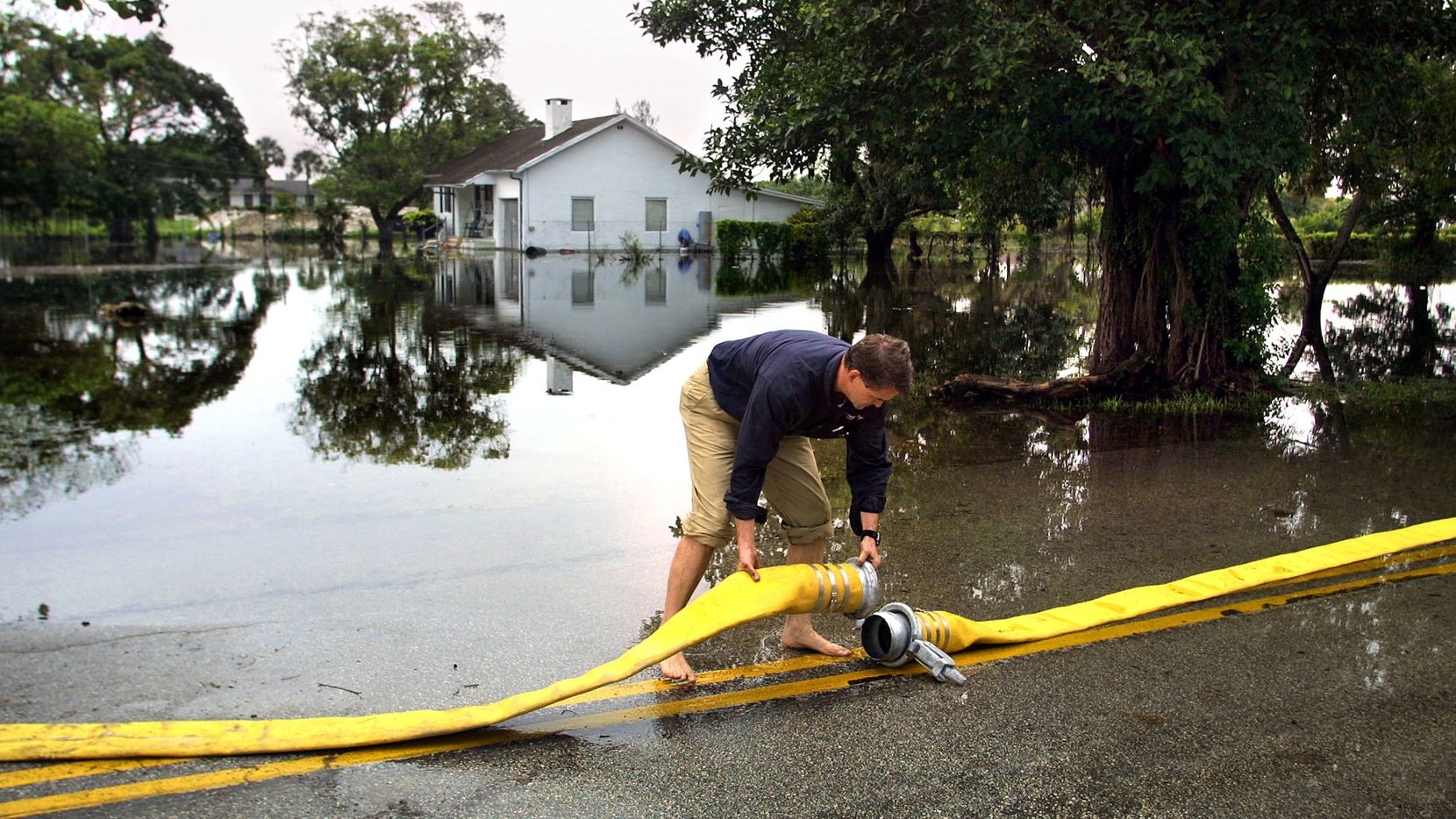 In this 2003 file photo, Jeff Cooper, district manager for United Rentals, a company hired by Broward County, connects sections of a 6-inch hose to help pump out floodwaters in a neighborhood in unincorporated Broward County, Fla., near Fort Lauderdale.