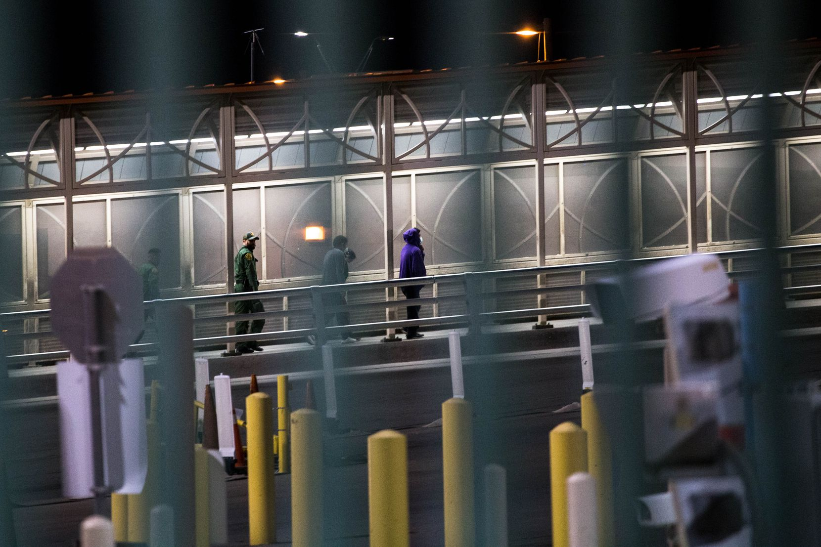 U.S. Border Patrol agents escort travelers back to Ciudad Juarez, Mexico, after rejecting their entry into the U.S. through the Paso Del Norte Port of Entry in El Paso in the early hours of Saturday, March 21, 2020.