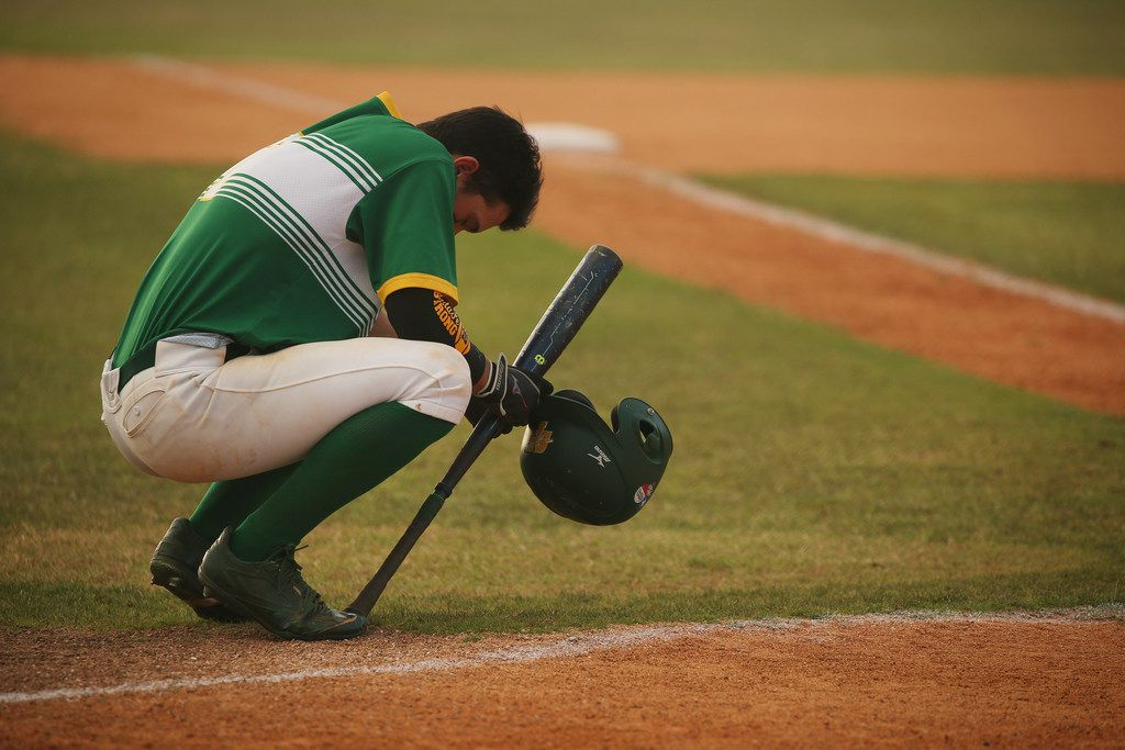 Santa Fe player Tyler Martin takes a moment before first at bat of the game during the second game of the best-of-three series in the Class 5A Region III playoff high school baseball game between Santa Fe and Kingwood Park at Jim Kethan Field at Deer Park High School in Deer Park, TX Saturday May 19, 2018. On Friday morning, 10 people were killed and 13 were injured after a shooting at Santa Fe High School. The game was postponed to Saturday after it was scheduled for Friday. Dimitrios Pagourtzis was booked into the Galveston County Jail on capital murder charges.