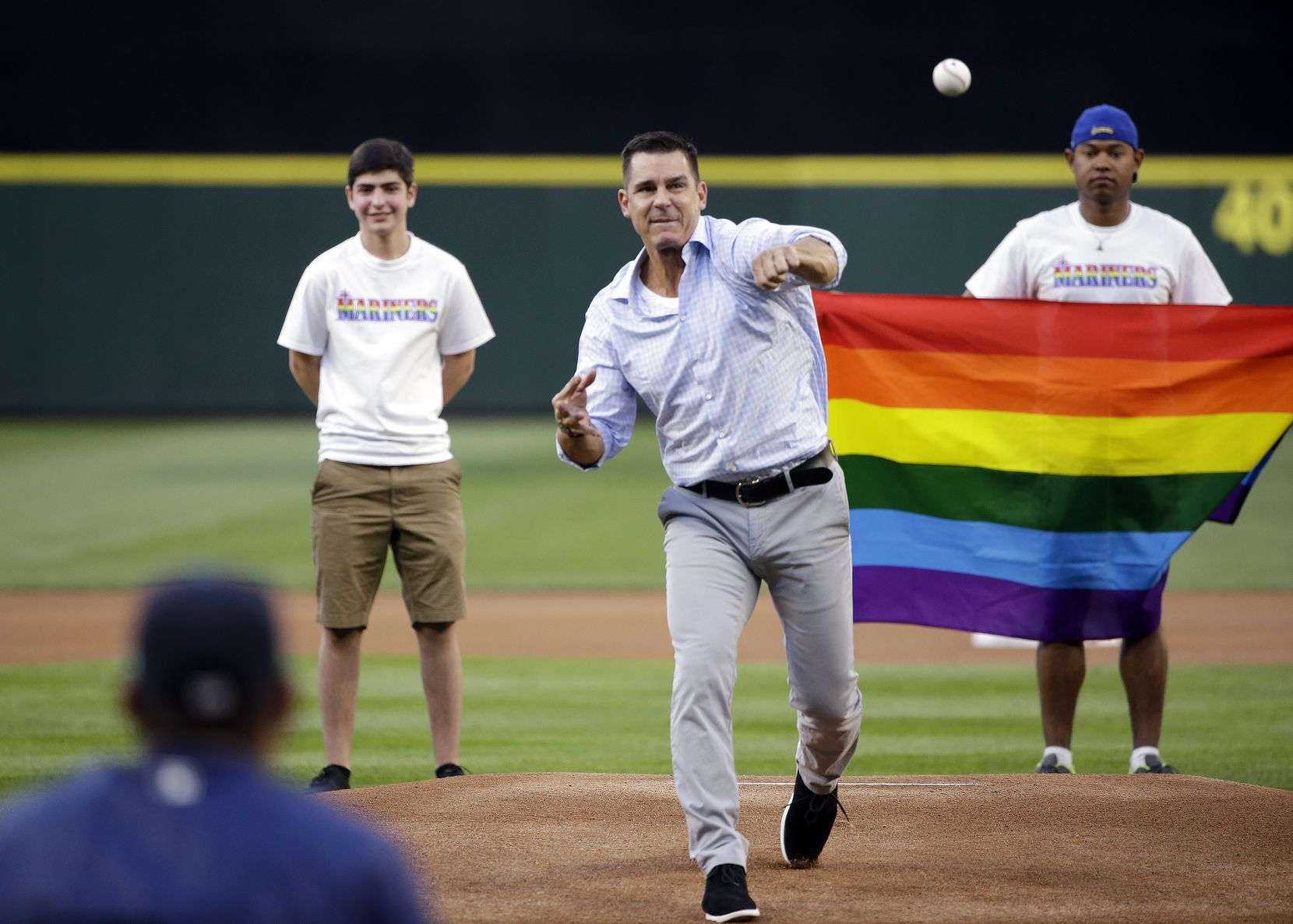 Billy Bean, Major League Baseball vice president of Social Responsibility & Inclusion, throws out the ceremonial first pitch to Seattle Mariners' Felix Hernandez before a baseball game between the Mariners and Milwaukee Brewers Friday, Aug. 19, 2016, in Seattle. The Mariners were celebrating LGBTQ Pride Night at the ballpark.