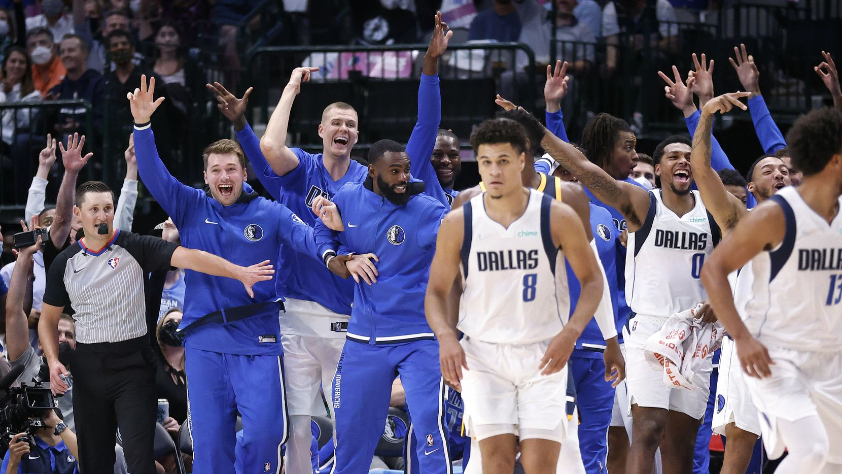 (from left) The Dallas Mavericks bench including (from left) guard Luka Doncic, center Kristaps Porzingis and forward Tim Hardaway Jr. celebrate after center Boban Marjanovic hit a second half three-pointer against the Utah Jazz at the American Airlines Center in Dallas, Wednesday, October 6, 2021. The Mavericks defeated the Jazz, 111-101.