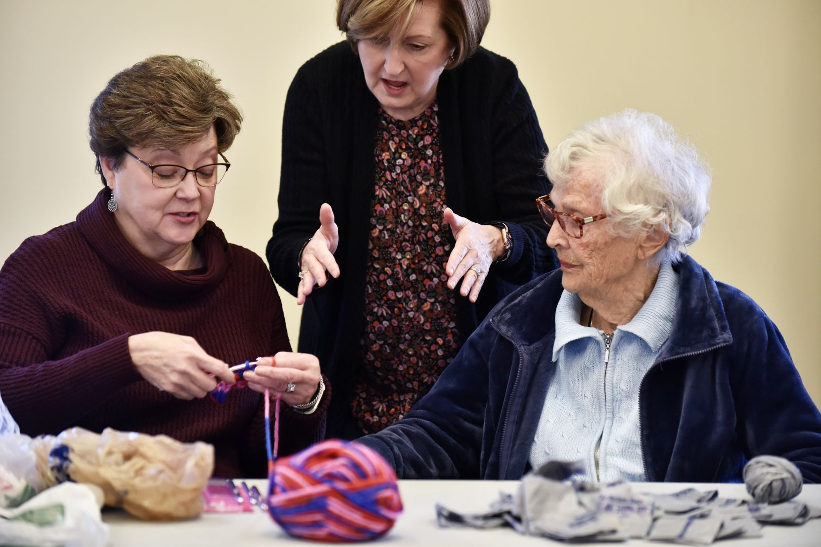 Kay McCall (from left), 62, learns to crochet from Kristi Jenkins, 63, and resident Emma Sattler, 92, at the CC Young Senior Living retirement community in Dallas.