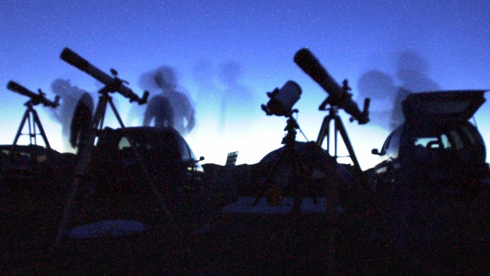 In this 2001 time-exposure file photo, amateur astronomers peer into their telescopes.