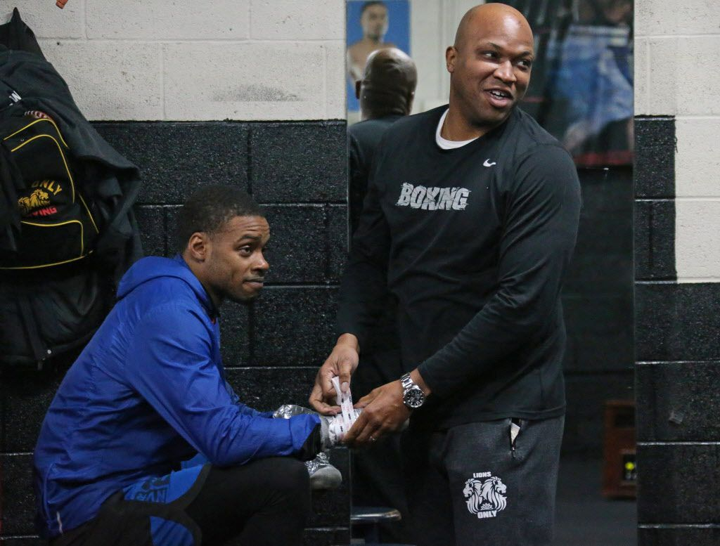 Trainer Derrick James, right, tapes up the wrists of boxer Errol Spence Jr. before their workout at R&R Boxing Club in Dallas on Friday, December 22, 2017. (Louis DeLuca/The Dallas Morning News)