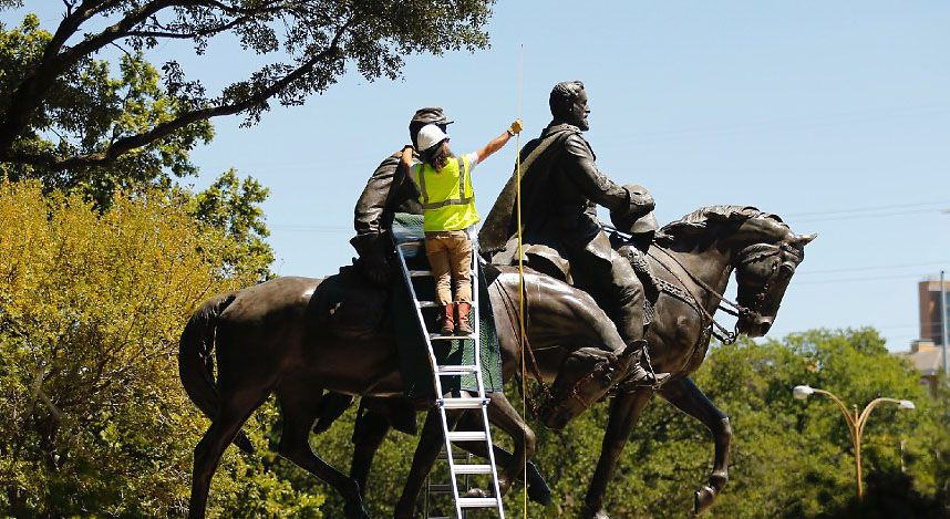 A crewman measure the height of the Robert E. Lee statue as they prepare to remove it from Robert E. Lee Park in Dallas, Wednesday, September 6, 2017. Earlier in the day the Dallas City Council voted 13-1 for the immediate removal of the monument of the statue to the Confederate general with a soldier at his side.