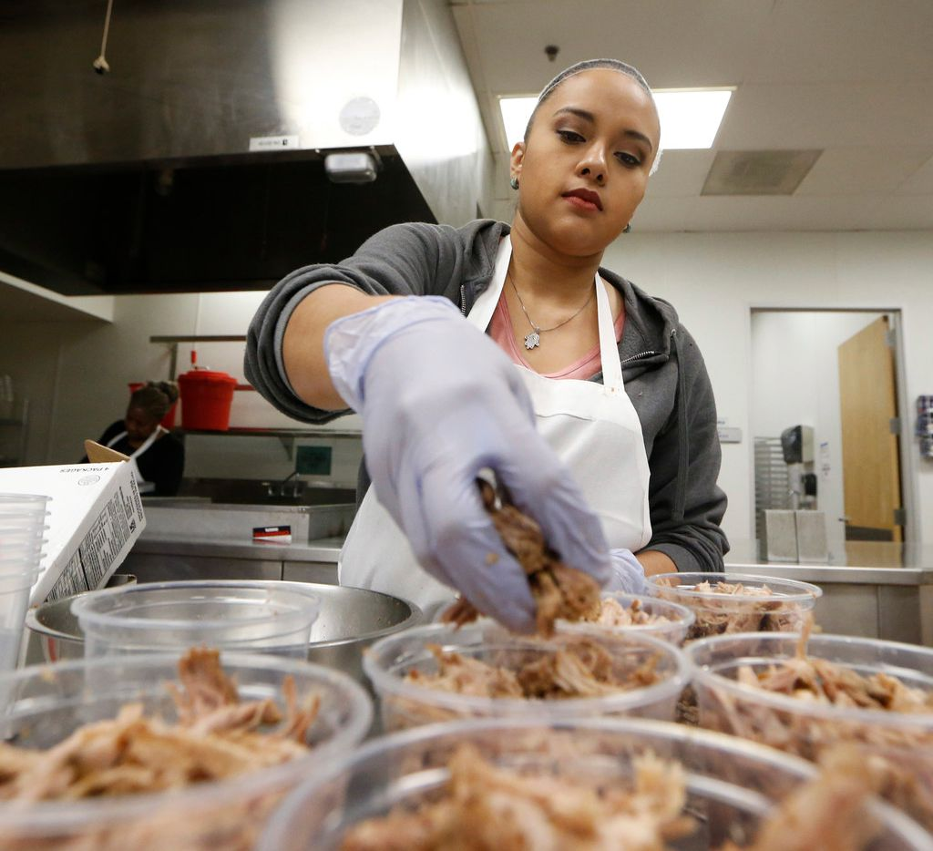 Stephanie Vasquez sorts pork out for Empanada Cookhouse at Pilotworks in Dallas.