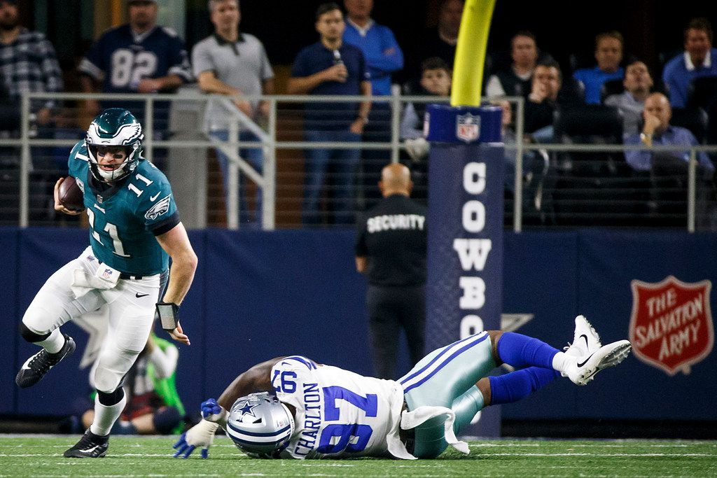 Philadelphia Eagles quarterback Carson Wentz (11) gets past Dallas Cowboys defensive end Taco Charlton (97) during the second half of an NFL football game at AT&T Stadium on Sunday, Nov. 19, 2017, in Arlington, Texas. The Eagles won the game 37-9. (Smiley N. Pool/The Dallas Morning News)