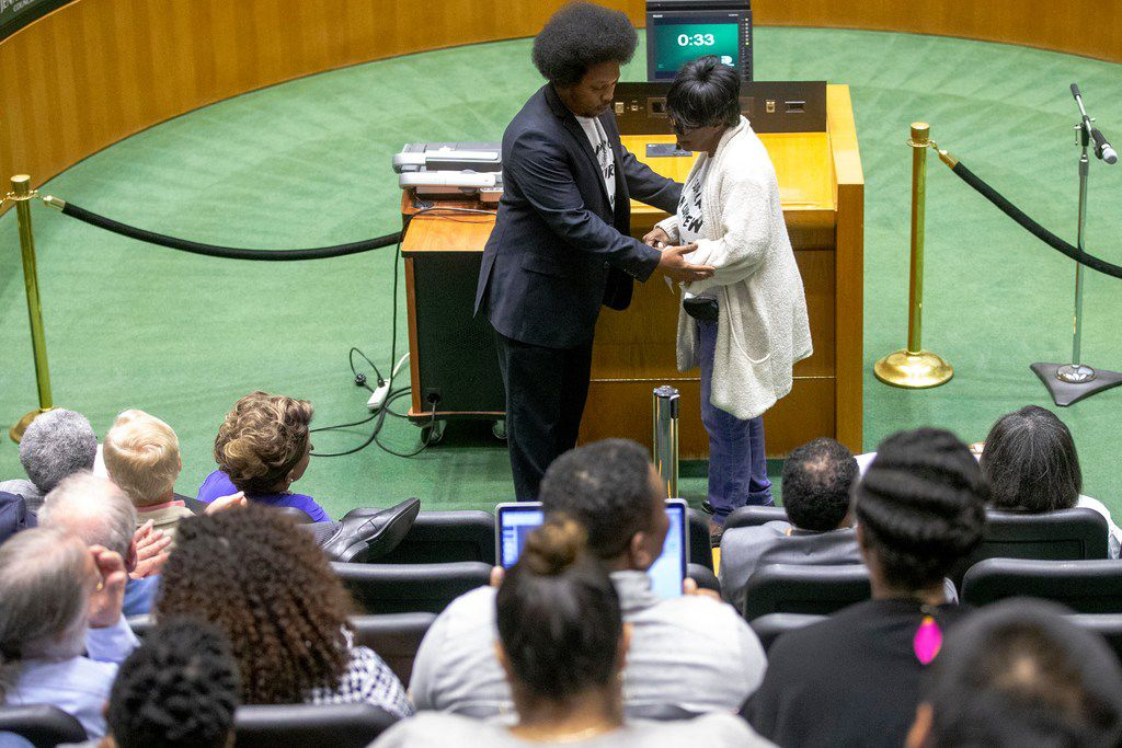 Andre Butler helps Edna Pemberton back to her seat after giving remarks during a previous juvenile curfew public hearing at Dallas City Hall on Wednesday, Feb. 6, 2019. (Shaban Athuman/The Dallas Morning News)