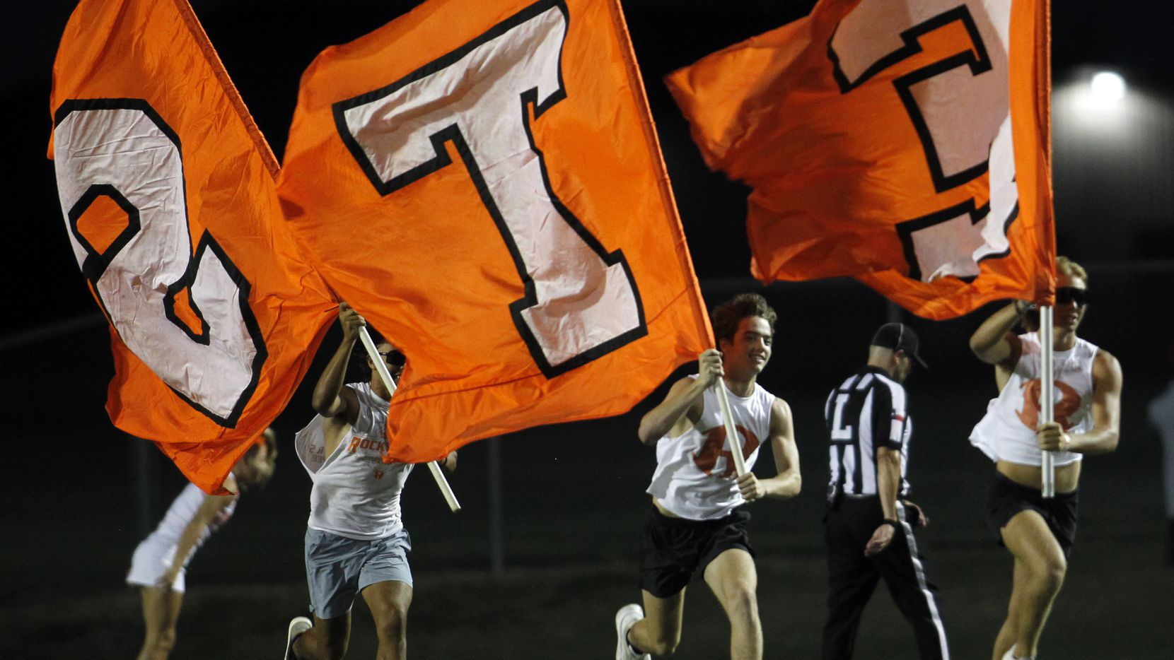Rockwall flag wavers sprint across the field following a first half yellow-jackets touchdown in their game against Cedar Hill. The two teams played their season opening football game at Longhorn Stadium in Cedar Hill on August 27, 2021. (Steve Hamm/ Special Contributor)