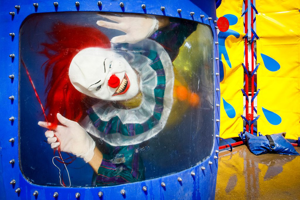 """Wearing a clown costume, Cornea Associates Dr. Tyrone McCall peers out from under the water of a dunking booth during the organization's employee appreciation week """"Cornea Carnival"""" on Friday, Sept. 15, 2017, in Dallas."""