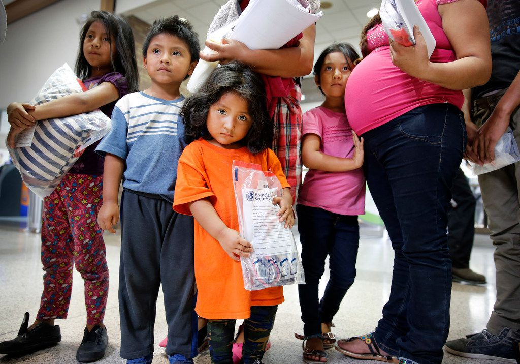 Cristle Ordoñez, 2, (center) and her brother Christian Ordoñez, 5, (second from left) and sister Jazmine Ordoñez, 7, (left) wait in line with their mother Ingrid Yanet Lopez Hernandez, 32, of Guatemala after being dropped off on a pair of government buses to the Central Station bus terminal in downtown McAllen, Texas, Sunday, June 24, 2018.  They were joined by Marcelda Mejilla, 6, who leans on her pregnant mother Meregilda Mejilla, 27. These Guatemalan immigrants were processed by the U.S. Border Patrol and dropped off at the bus terminal. From there the families were gathered up by the Catholic Charities of the Rio Grande Valley and walked to their location a few blocks away. There they can get cleaned up, fed and receive help getting transportation to their future destinations. (Tom Fox/The Dallas Morning News)