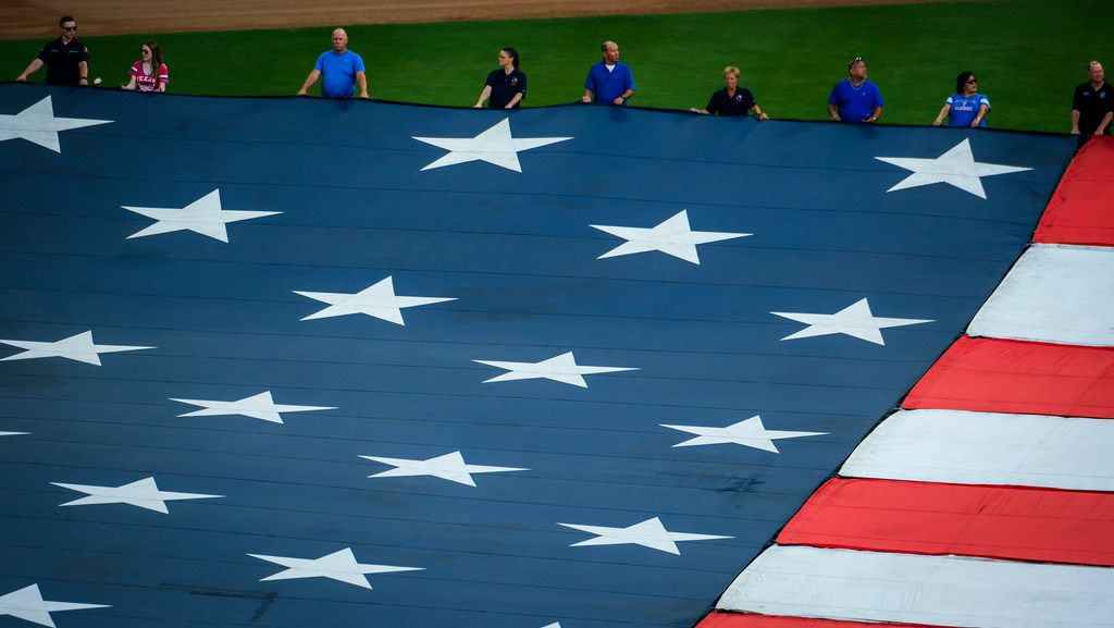 First responders from the Arlington police and fire departments unfurl large US flag at Globe Life Park before a game between the Texas Rangers and the Tampa Bay Rays on Wednesday, Sept. 11, 2019, in Arlington. (Smiley N. Pool/The Dallas Morning News)