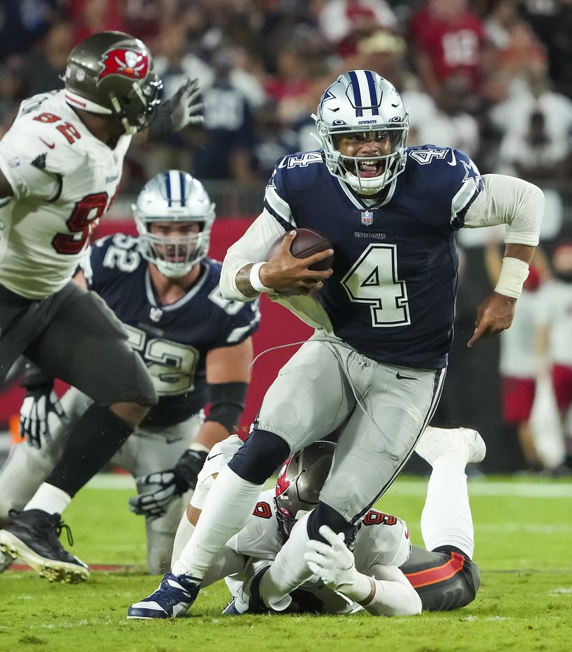 Dallas Cowboys quarterback Dak Prescott (4) is tripped up by Tampa Bay Buccaneers linebacker Joe Tryon-Shoyinka (9) during the first half of an NFL football game at Raymond James Stadium on Thursday, Sept. 9, 2021, in Tampa, Fla. (Smiley N. Pool/The Dallas Morning News)