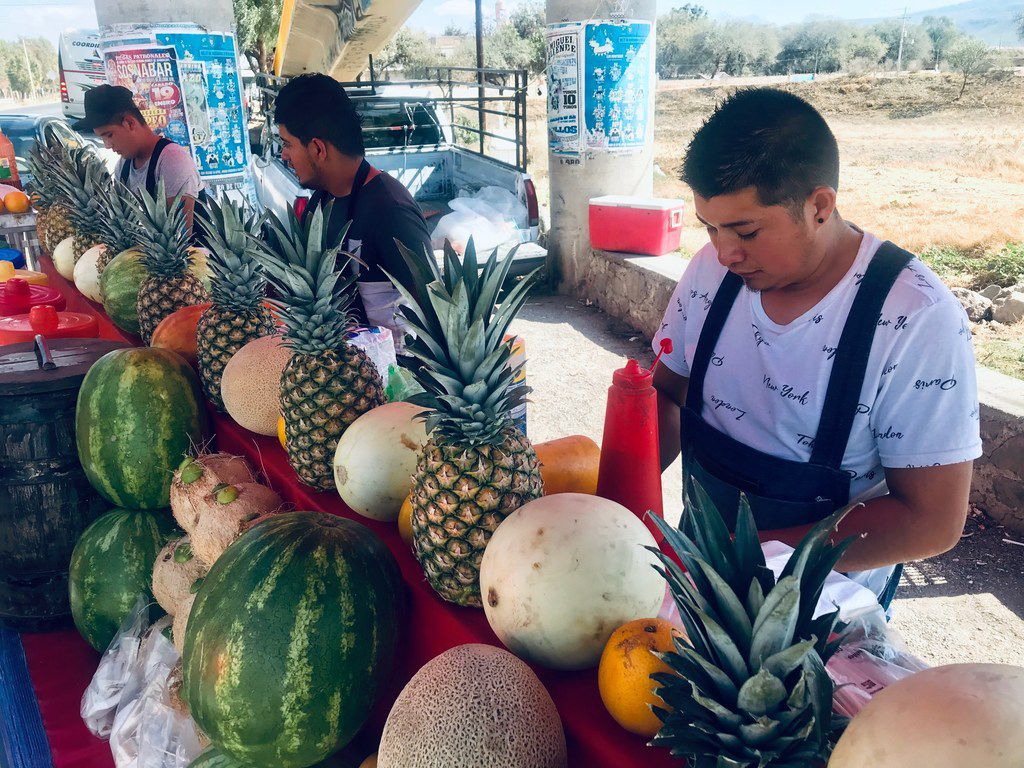 Jairo Villalon (left), 21, works alongside his friends, brothers Carlos Padilla (right), 21, and Rigoberto Padilla, 18, running a fruit stand between San Miguel de Allende and Queretaro, Mexico, on a weekend in February 2019. All three expressed no desire to migrate to Texas, a sharp contrast from past family members who saw the U.S. as their best option in getting ahead.