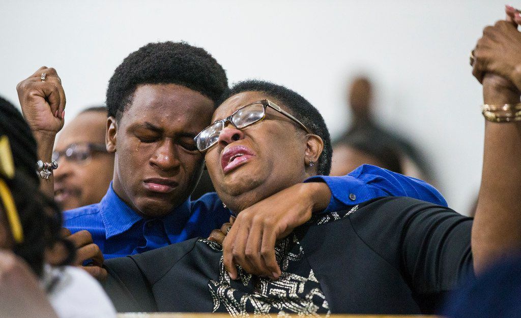 Allison Jean raises her hands in the air as she leans on her son, Brandt, during a prayer service for her son and Brandt's brother, Botham Shem Jean, at the Dallas West Church of Christ on Sept. 9, 2018.