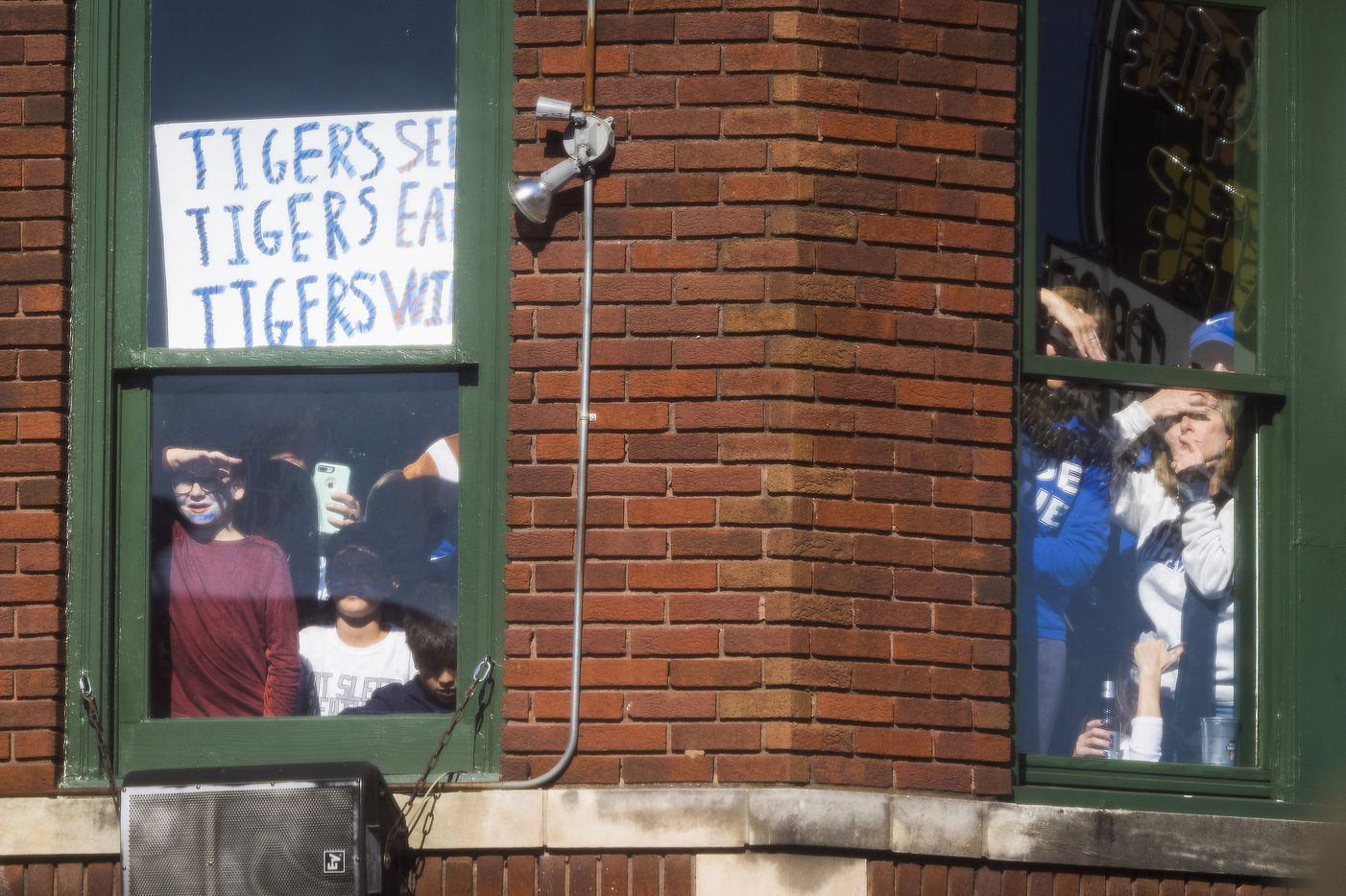 Fans looks out second floor windows to watch a ESPN College GameDay on Beale Street before an NCAA football game between Memphis and SMU on Saturday, Nov. 2, 2019, in Memphis, Tenn.