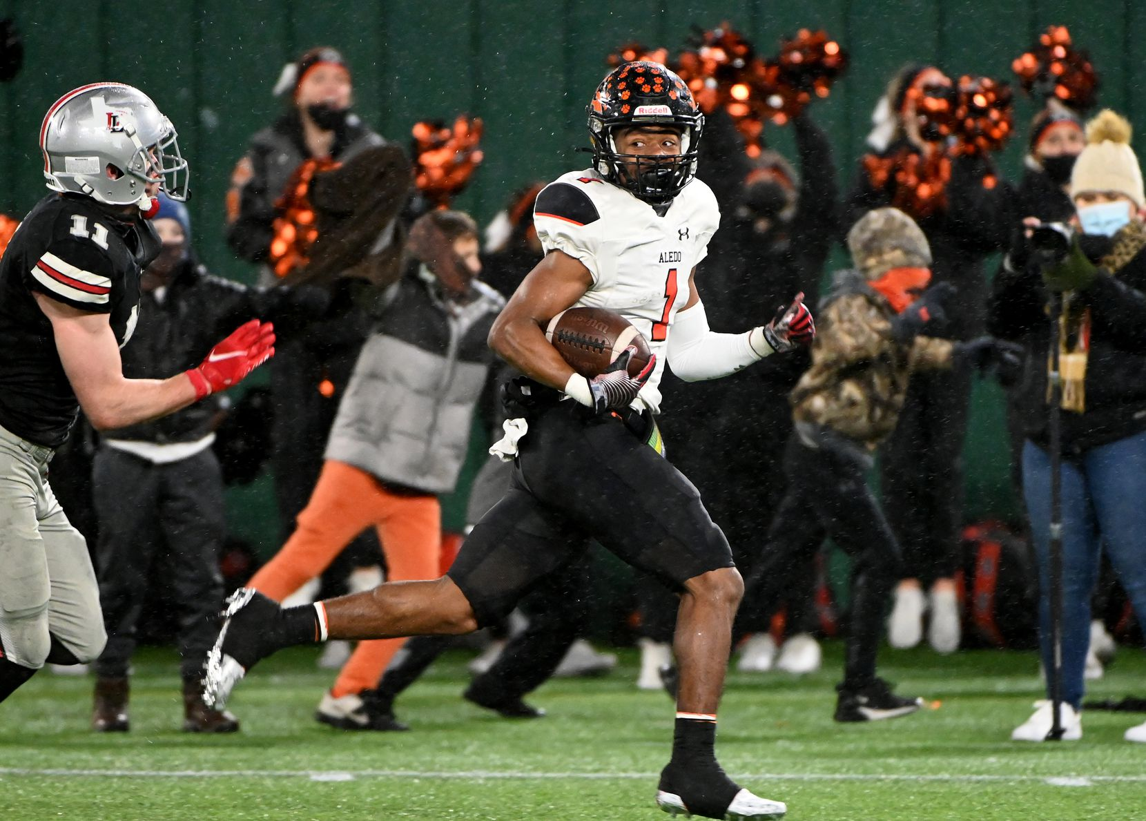 Aledo's Jo Jo Earle (1) runs past Lovejoy's Chief Collins for a touchdown in the first quarter of a Class 5A Div. II Region II final on Friday, Jan. 1, 2021, in Arlington.