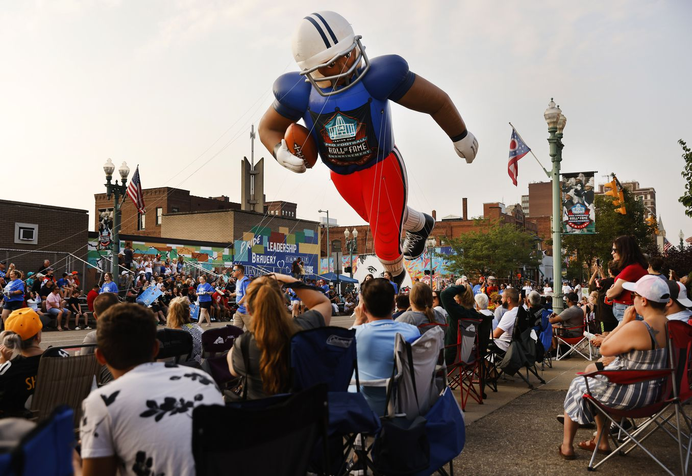 NFL fans watch as a large inflatable football player floats down Cleveland Ave. during the Canton Repository Grand Parade in downtown Canton, Ohio, Saturday, August 7, 2021. The Pro Football Hall of Fame parade honored newly elected and former members of the Hall, including newcomers and former Dallas Cowboys players Cliff Harris, Drew Pearson and head coach Jimmy Johnson. (Tom Fox/The Dallas Morning News)