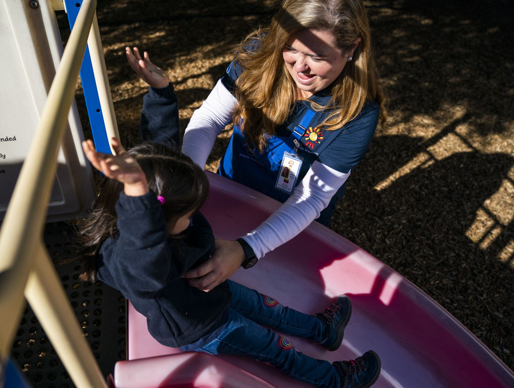 Teacher Alecia Gonzalez helps Natalia Lopez-Tafoya, 3,  down a slide on the playground on Nov. 18, 2019, at Spanish Schoolhouse in Coppell. Gonzalez is among several Venezuelan teachers at the Spanish-speaking preschool.